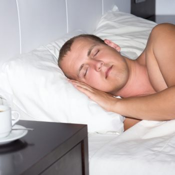sleeping man and cup of coffee in bedroom