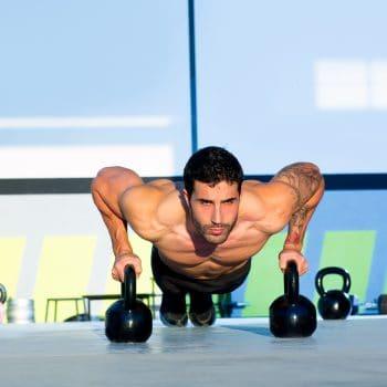 Mand træner armstrækninger med to sorte kettlebells